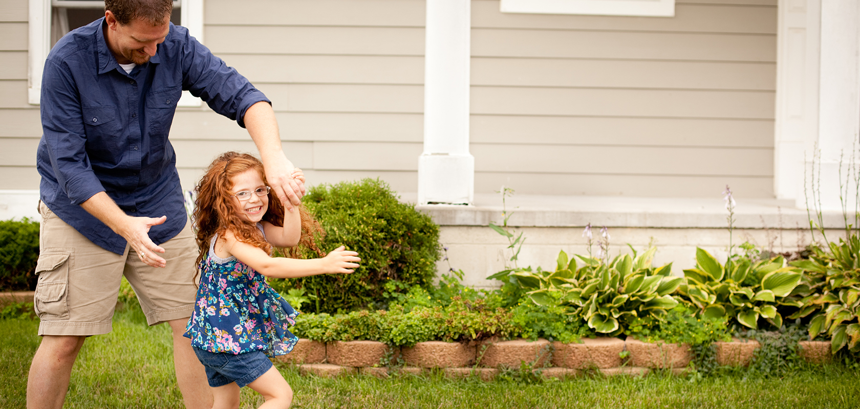 father dancing with daughter in yard