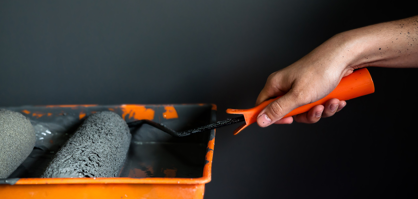 Close up of hand holding paint roller in paint tray, Grey wall background, Copy space.
