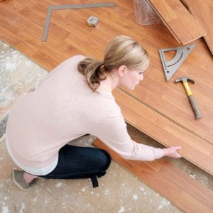 woman installing laminate flooring