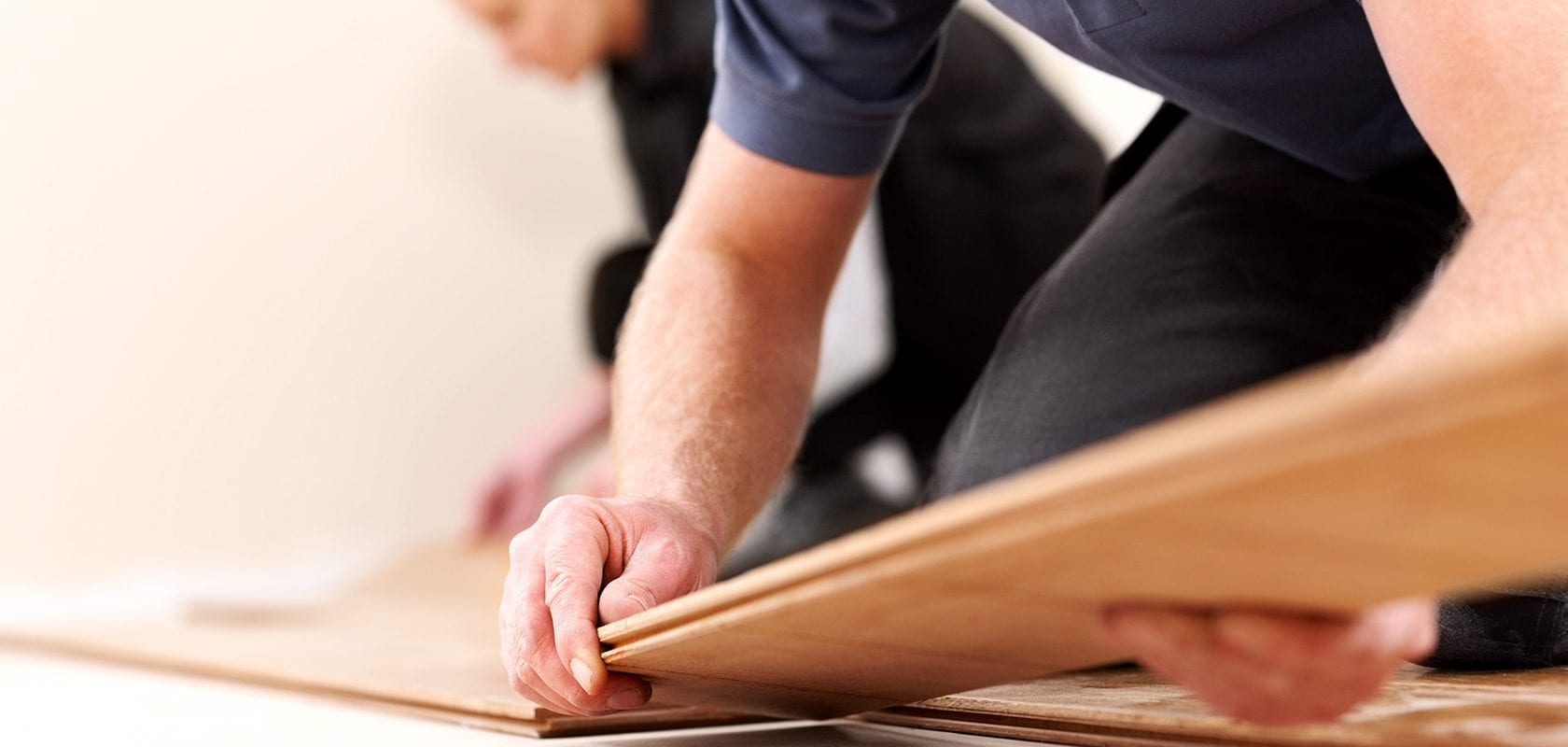 close up view of people installing laminate flooring